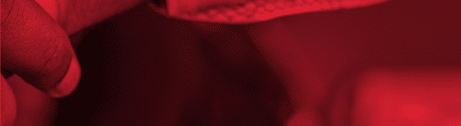 Roter Bildausschnitt von zwei einschlagenden Händen, bei dem nur ein Finger und das Stück eines Ärmels erkennbar ist.