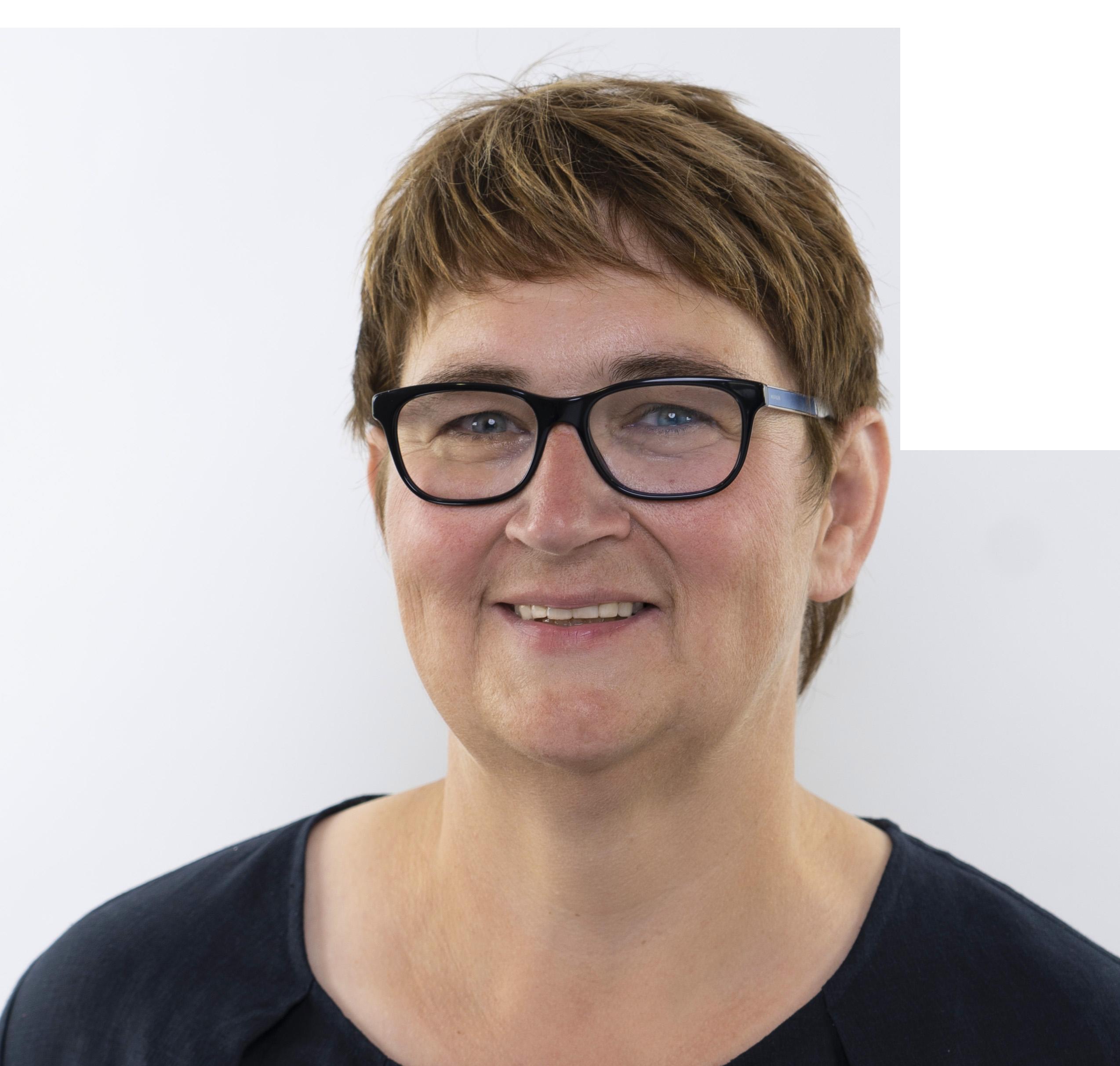 Eine Dame mit moderner, schwarzer Brille lächelt freundlich in die Kamera.