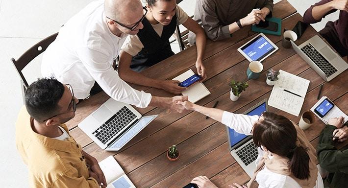 An einem Besprechungstisch sitzen mehrere Personen, die sich unterhalten und teilweise die Hände schütteln. Auf dem Tisch stehen mehrere technische Geräte, wie Laptops, Smartphones und Tablet PCs.