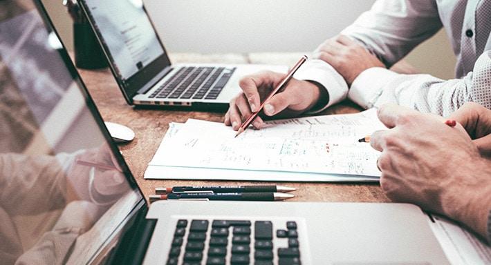 Auf einem Schreibtisch stehen zwei Laptops, vor denen jeweils eine Person sitzt. Zwischen den Laptops liegen mehrere Unterlagen, auf denen sich die beiden Personen Notizen machen.