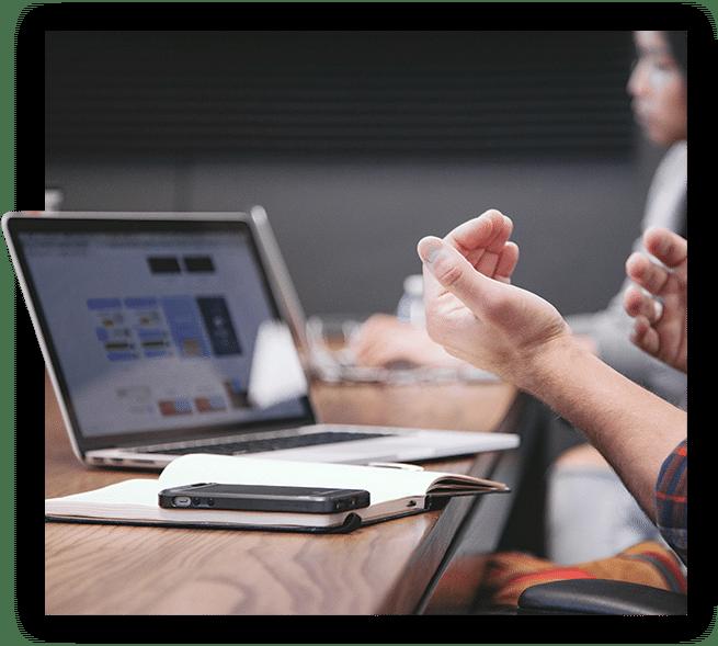 Auf einem Schreibtisch steht ein aufgeklappter Laptop, vor dem ein Notizbuch und ein Smartphone liegen. An dem Tisch sitzen mindestens zwei Personen, von denen eine im Hintergrund zu erkennen ist und eine im Vordergrund gestikuliert.