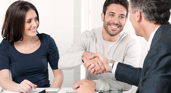 Drei Personen sitzen an einem Tisch. Eine Frau schaut lächelnd zwei Männer an, die sich die Hände schütteln.