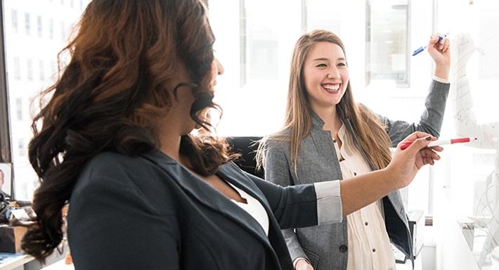 Zwei Damen stehen lachend mit jeweils einem Stift in der Hand vor einem Whiteboard.